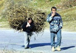 Homme fumant, laissant sa femme porter le fagot de bois.